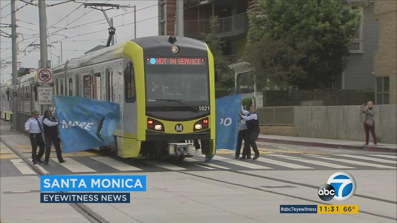 A Metro Expo Line train breaks through a ceremonial banner on the first day of public operation for the light-rail extension on Friday, May 20, 2016.