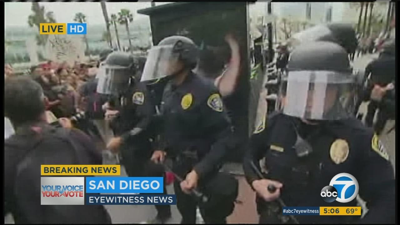 At least three people were arrested after protesters began throwing plastic bottles and trying to scale barricades outside a Donald Trump rally in San Diego.