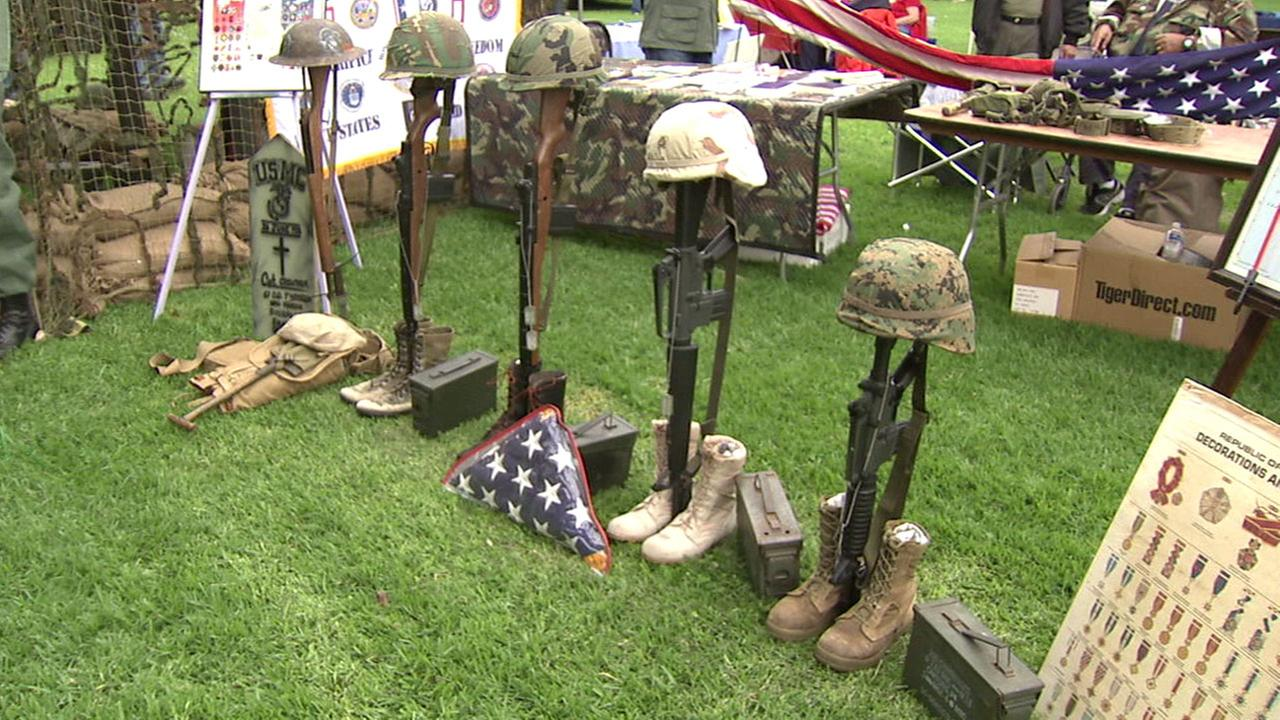 Guns and military hats honor fallen soldiers at a set up in Arcadia Community Park during a tribute event for Memorial Day weekend on Saturday, May 28, 2016.