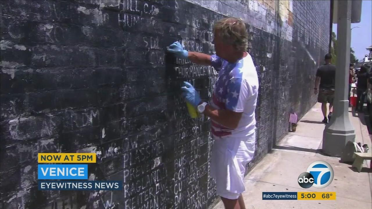 Community members clean a Vietnam War memorial wall in Venice vandalized on Memorial Day weekend Sunday, May 29, 2016.