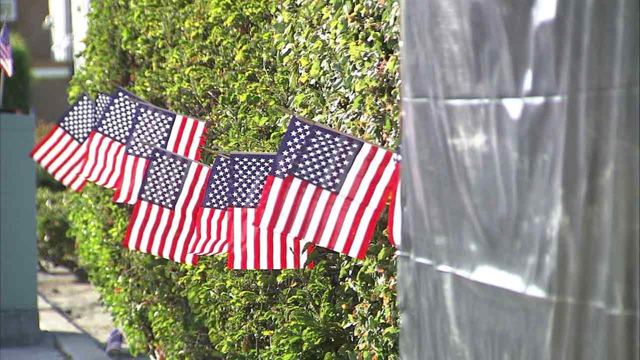 American flags are placed next to a Vietnam memorial wall in Venice that was covered up after it was tagged on Memorial Day weekend.