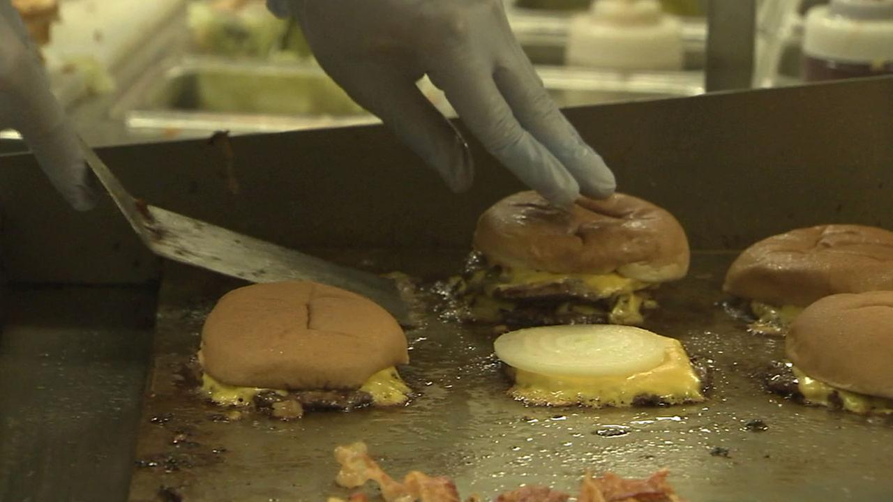 A cook assembles a cheeseburger at CaliBurger, a new restaurant opening in Pasadena in mid-June.