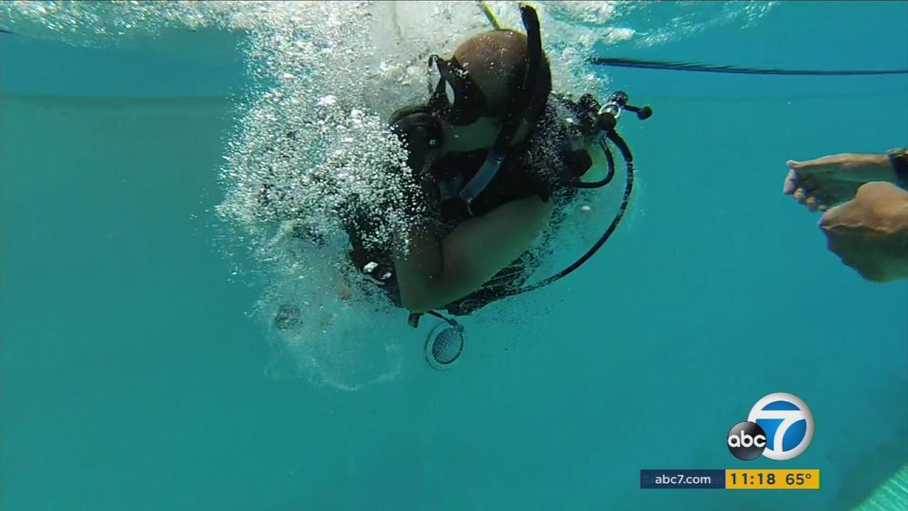 A wounded combat veteran dives into a pool during his scuba diving training in La Verne.