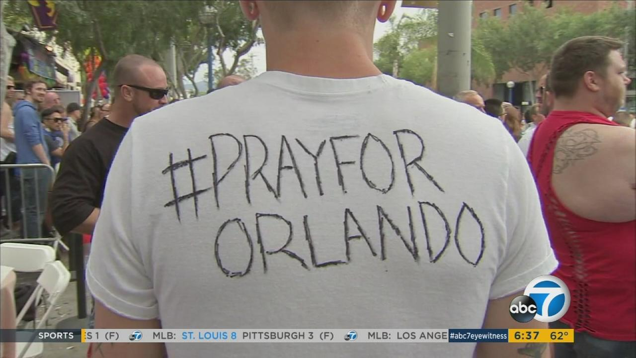 A man wears a white T-shirt with written words stating #PrayforOrlando following a deadly nightclub shooting that left at least 49 people dead early Sunday, June 12, 2016.