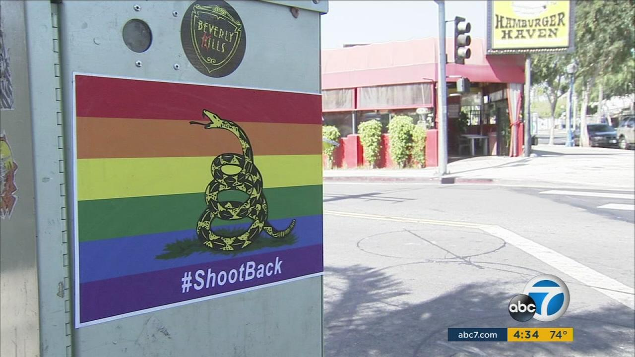 A photo depicting a coiled rattlesnake against a rainbow with the phrase #shootback is shown plastered all over West Hollywood.
