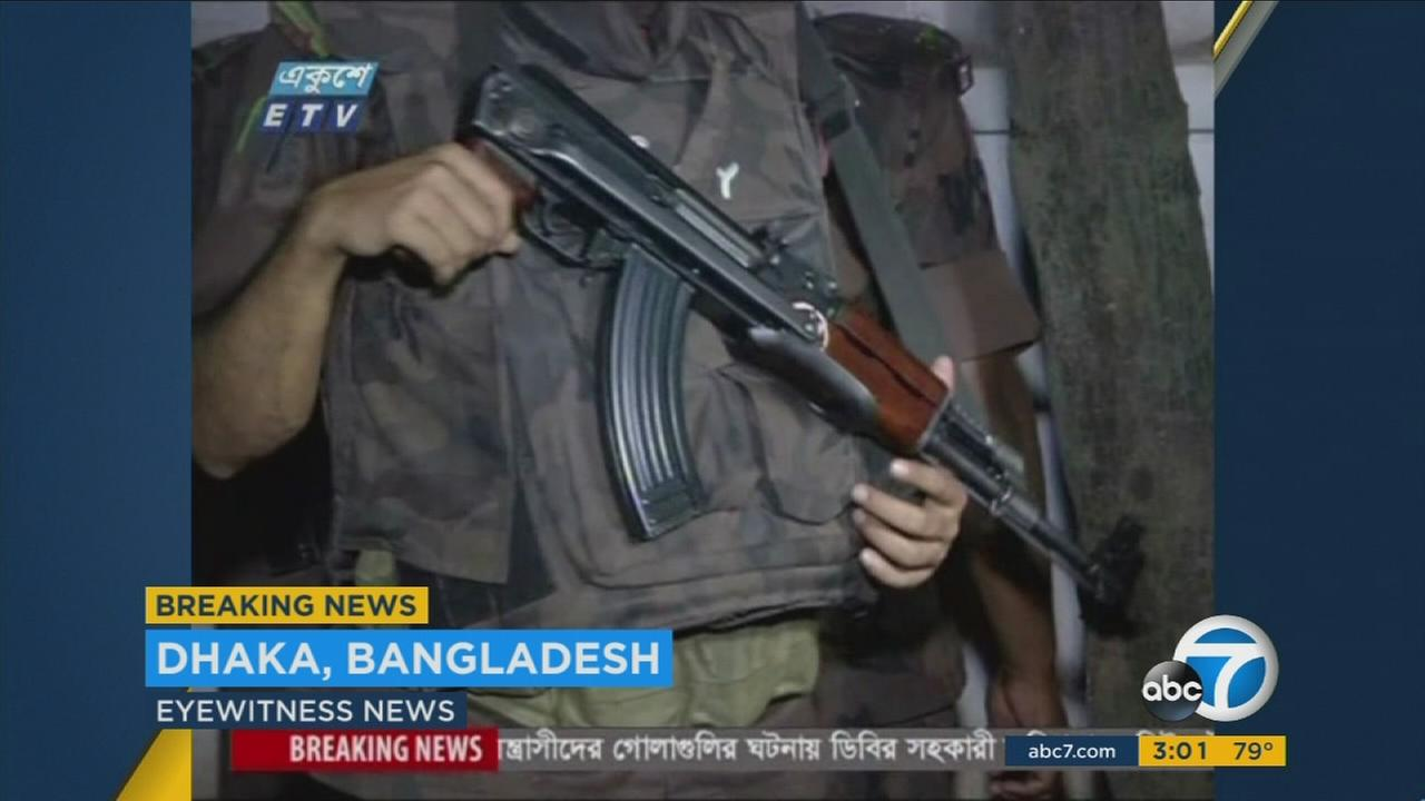 Men are seen carrying weapons after an attack at a cafe in Dhaka, Bangladesh.