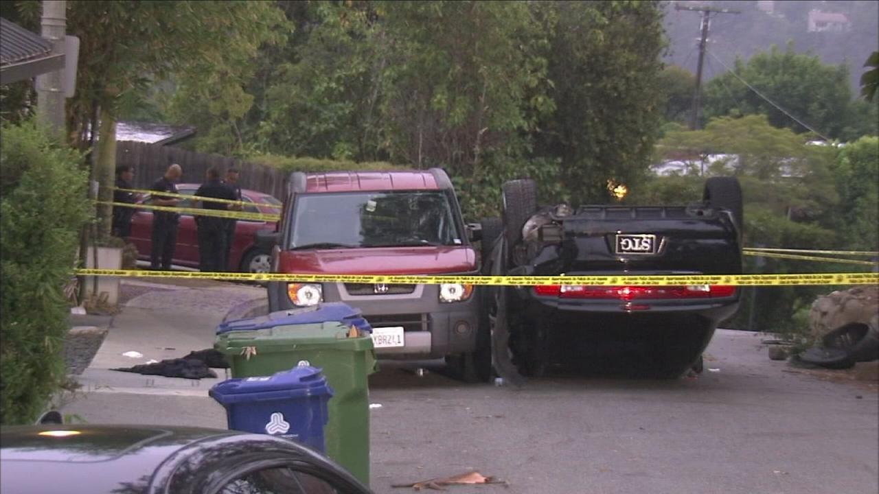 An overturned car is blocked off after the driver tried to flee a robbery attempt, flipped the car and was shot in the Hollywood Hills on Thursday, July 7, 2016.