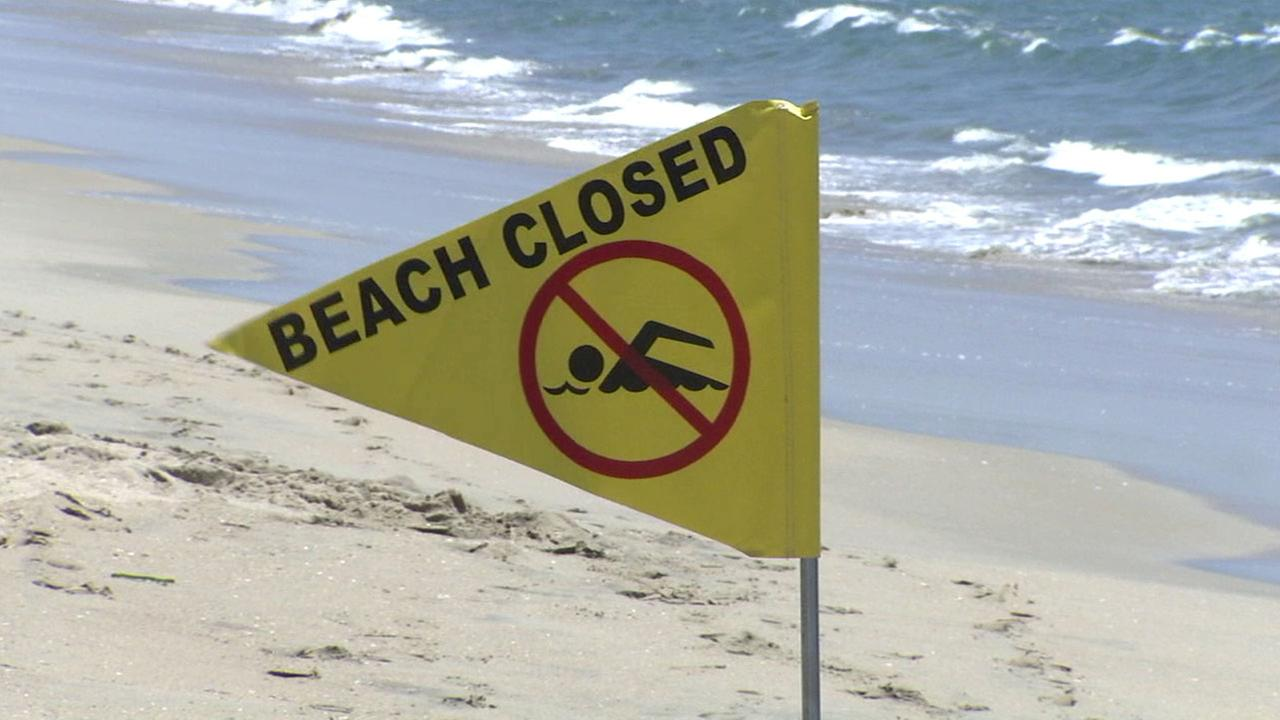 A flag warns beach goers to stay away from a Long Beach coast after a sewage spill may have contaminated the waters.