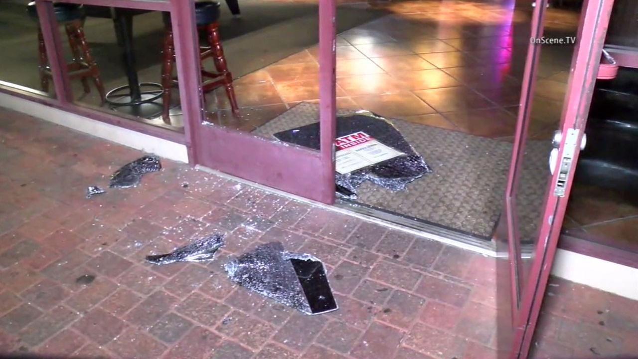 A smashed window at one of five restaurants struck in either La Habra or Whittier is shown.