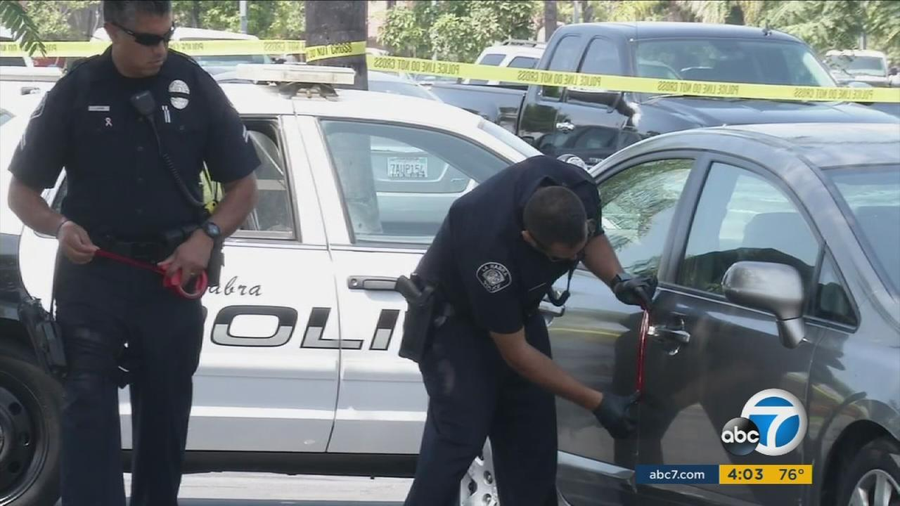 Authorities investigate the circumstances surrounding a woman whose body was found inside a car in a parking lot in La Habra on Friday, Aug. 5, 2016.
