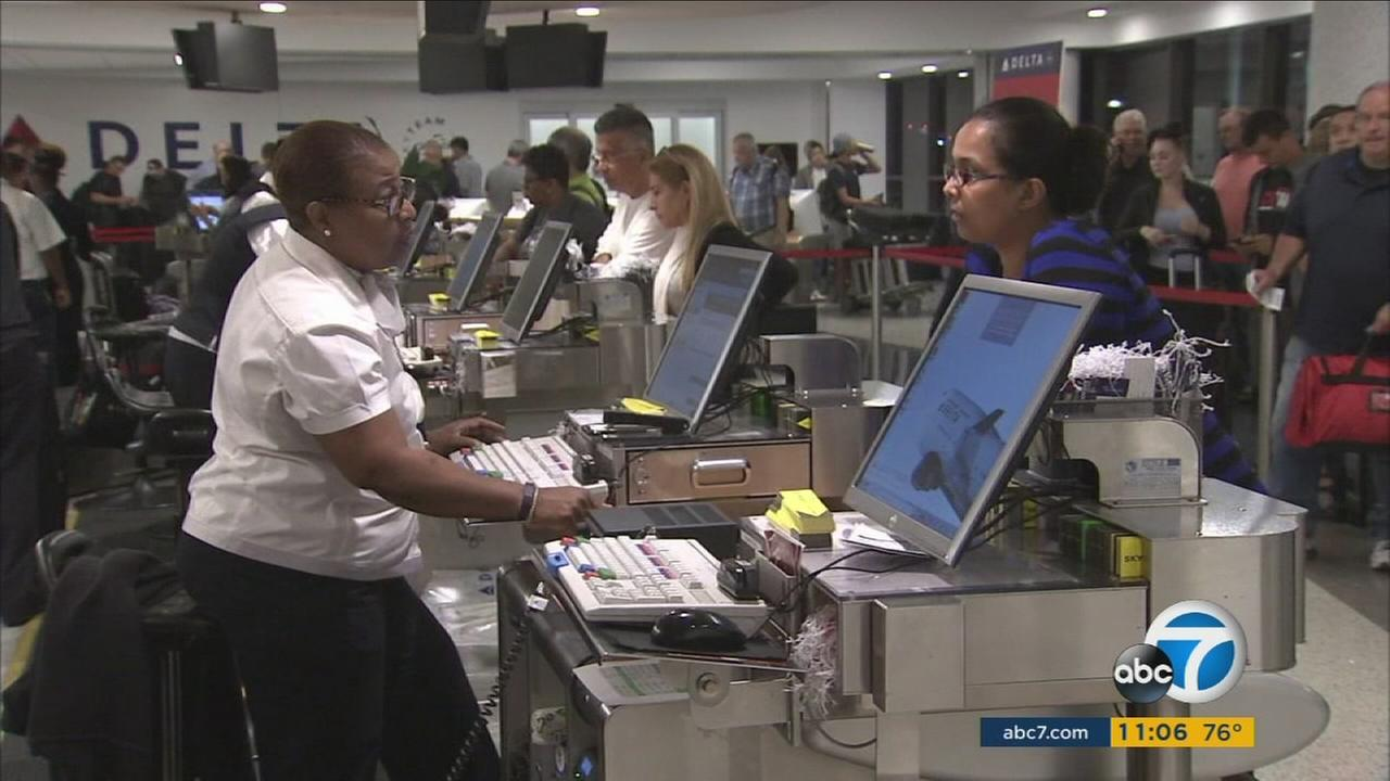 Delta customers at Los Angeles International Airport talk to airport employees after the airline experienced a worldwide systems outage on Monday, Aug. 8, 2016.