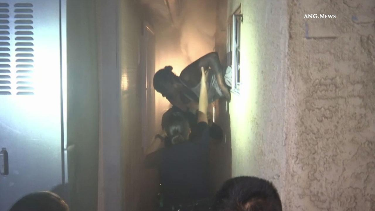 Officers and firefighters grab a woman and pull her out of a window as her Vermont Knolls home burned on Tuesday, Aug. 9, 2016.