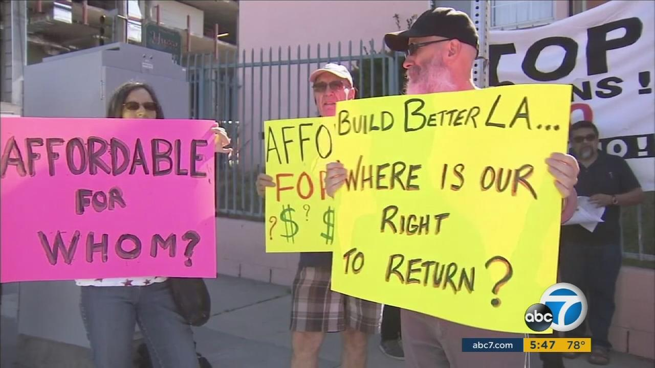 People hold up signs opposing a proposed rent hike at a senior living complex in Eagle Rock.