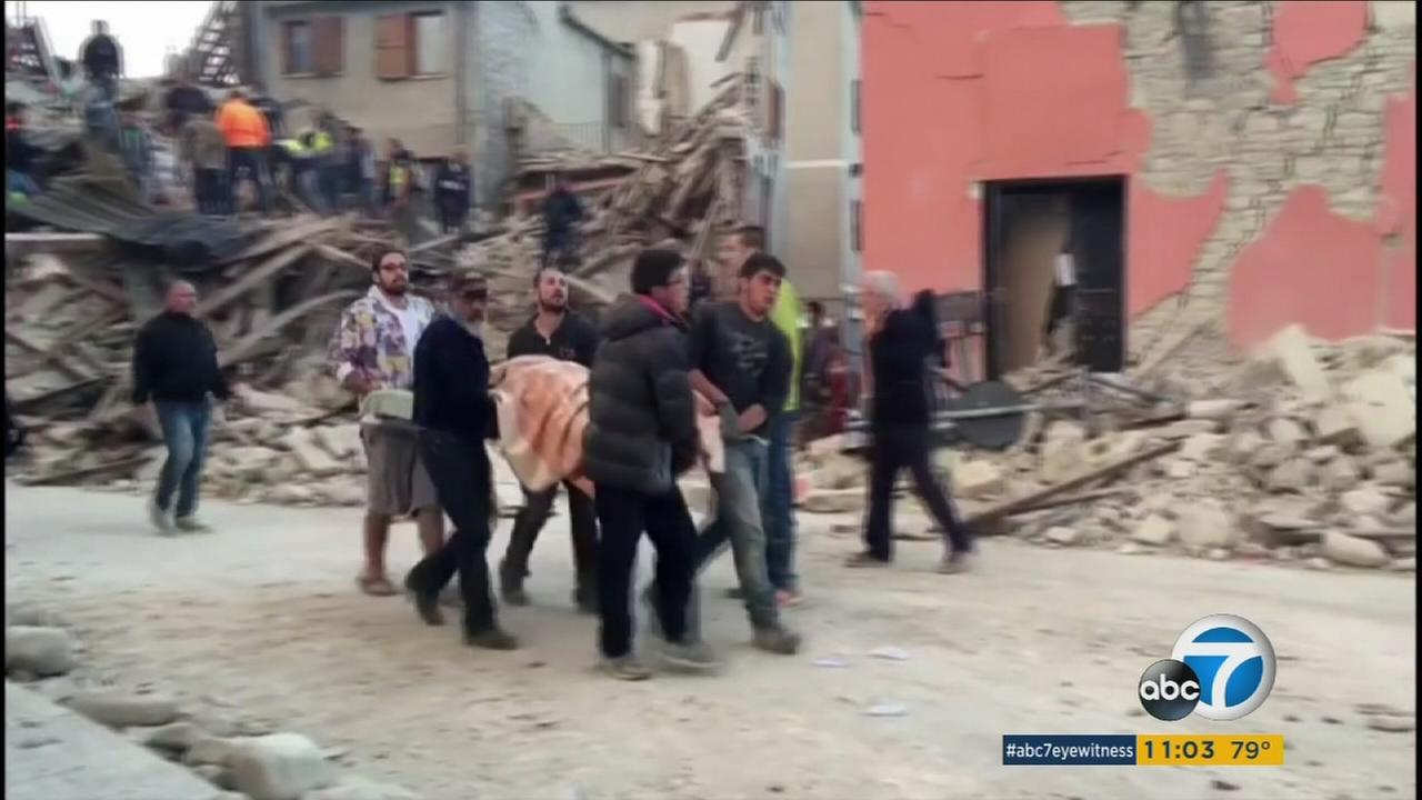 A group of men carry one of many casualties in the magnitude 6 quake that struck central Italy Wednesday, Aug. 24, 2016.