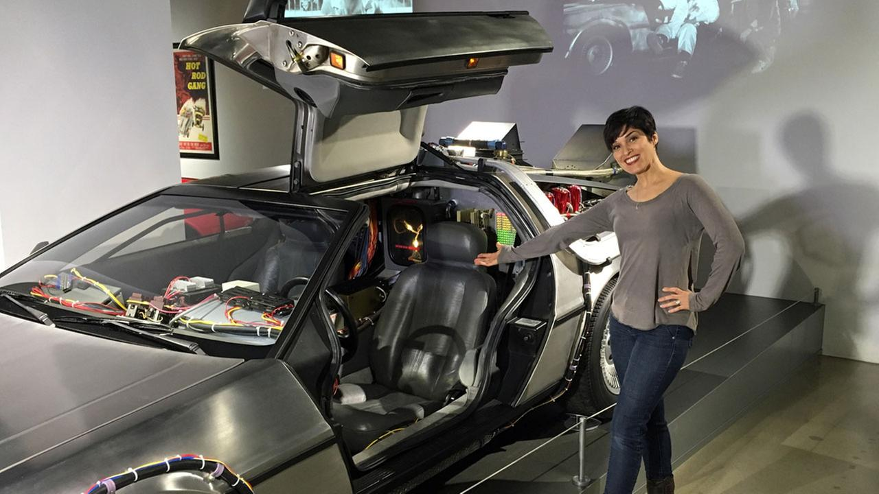 Eye on L.A. host Tina Malave poses next to a car at the Petersen Automotive Museum in Los Angeles.