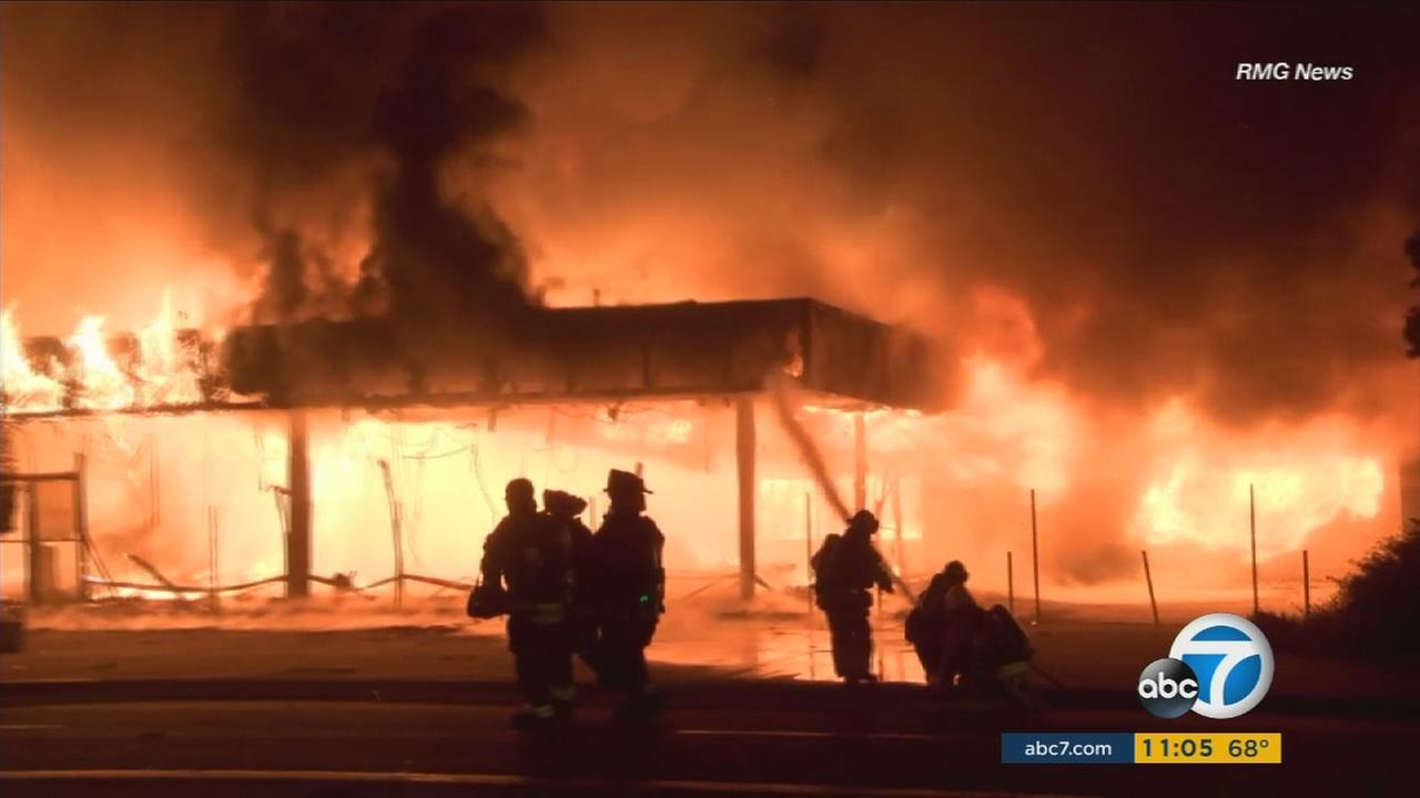 Firefighters are seen battling a blaze that ripped through an abandoned car dealership in Covina on Wednesday, Aug. 31, 2016.
