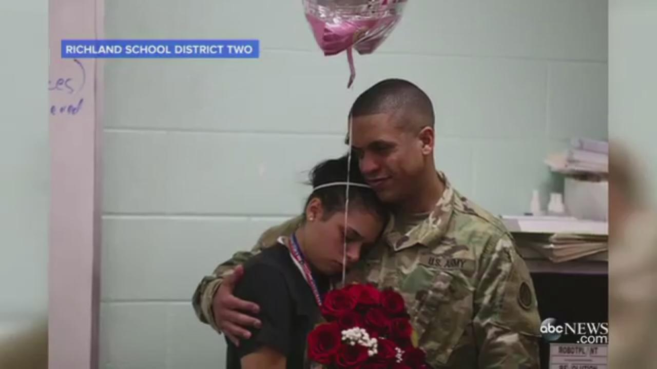 Sgt. Carlos Solis hugs his daughter Solymar after surprising her at her South Carolina high school.
