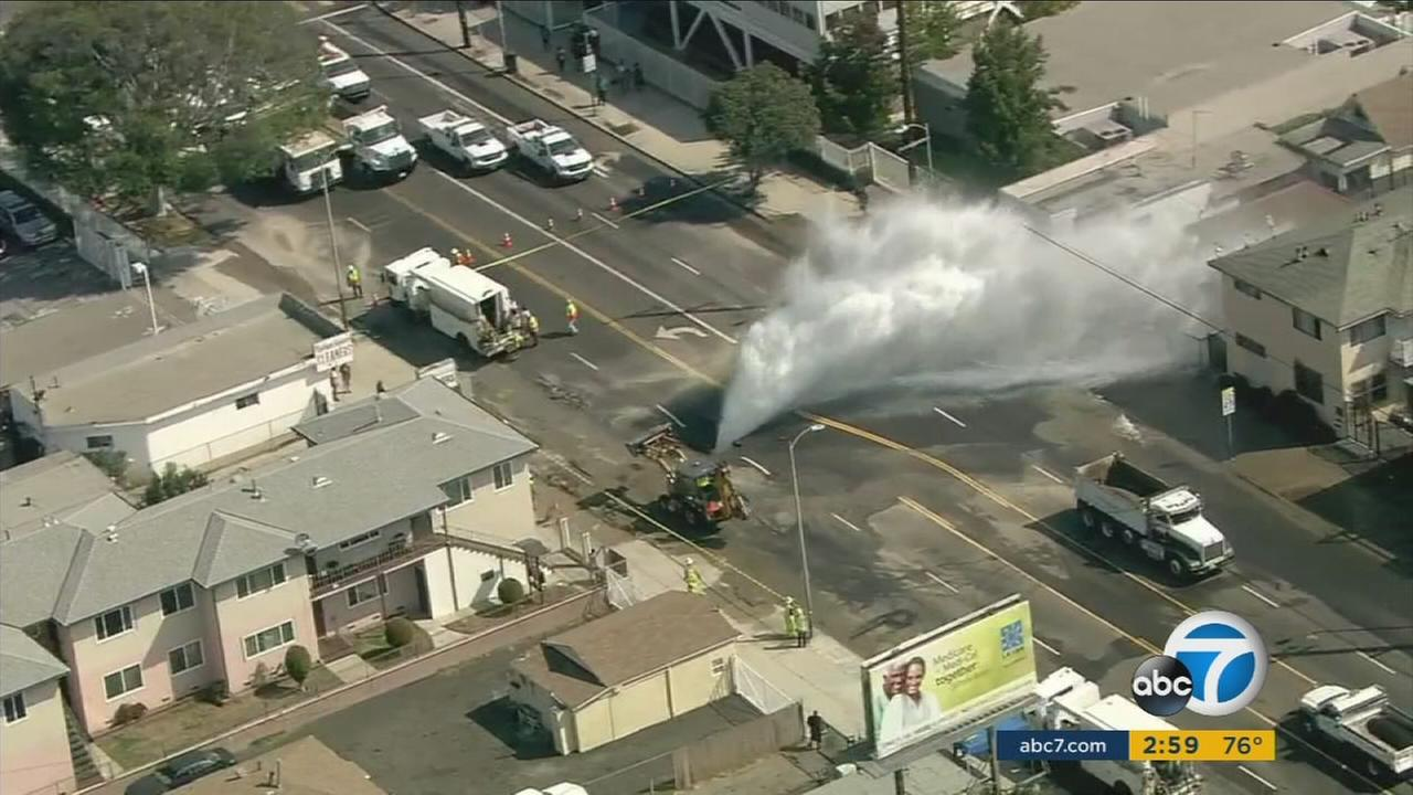 A 12-inch water main ruptured below a street in South Los Angeles on Wednesday, Sept. 7, 2016, resulting in a gusher that doused several nearby structures.