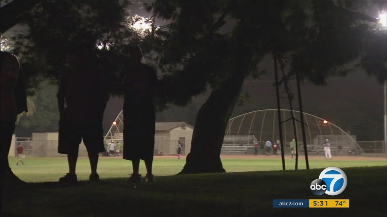 In this undated photo, two people are seen standing in the shadows as kids play at an Anaheim park.