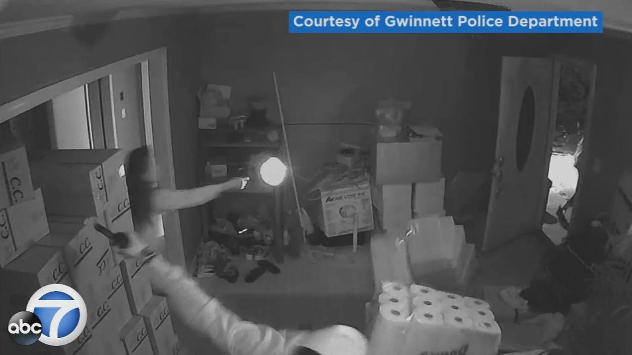 Dramatic surveillance video captures a Georgia woman turning the tables on three armed people who broke into her home.