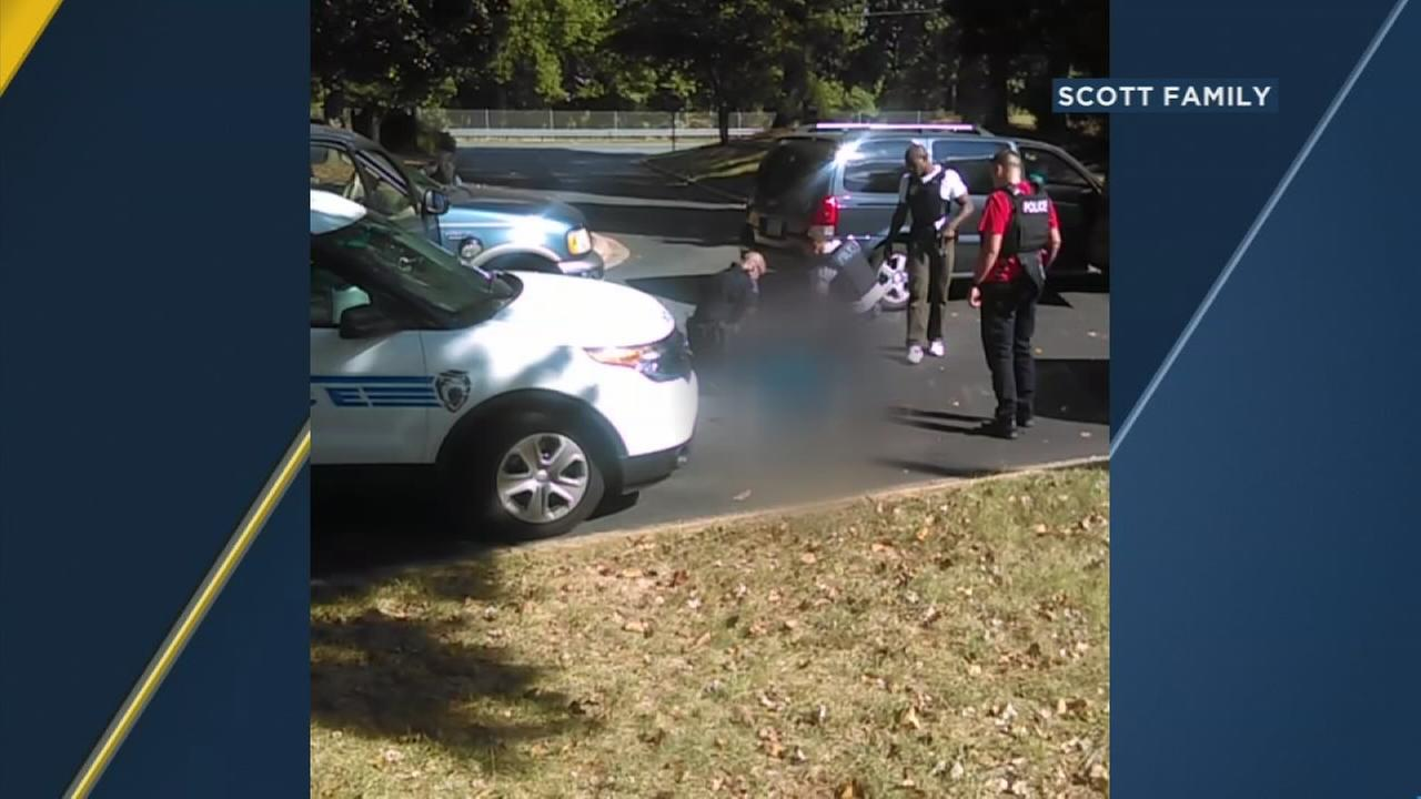 Video of a deadly encounter between Charlotte police and a black man shows his wife repeatedly telling officers he is not armed and pleading with them not to shoot.