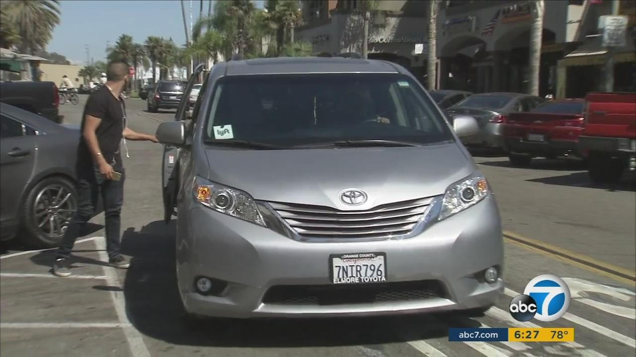 A person is dropped off by a Lyft driver, who stopped in the middle of Main Street in Huntington Beach, which has caused concern for peoples safety.