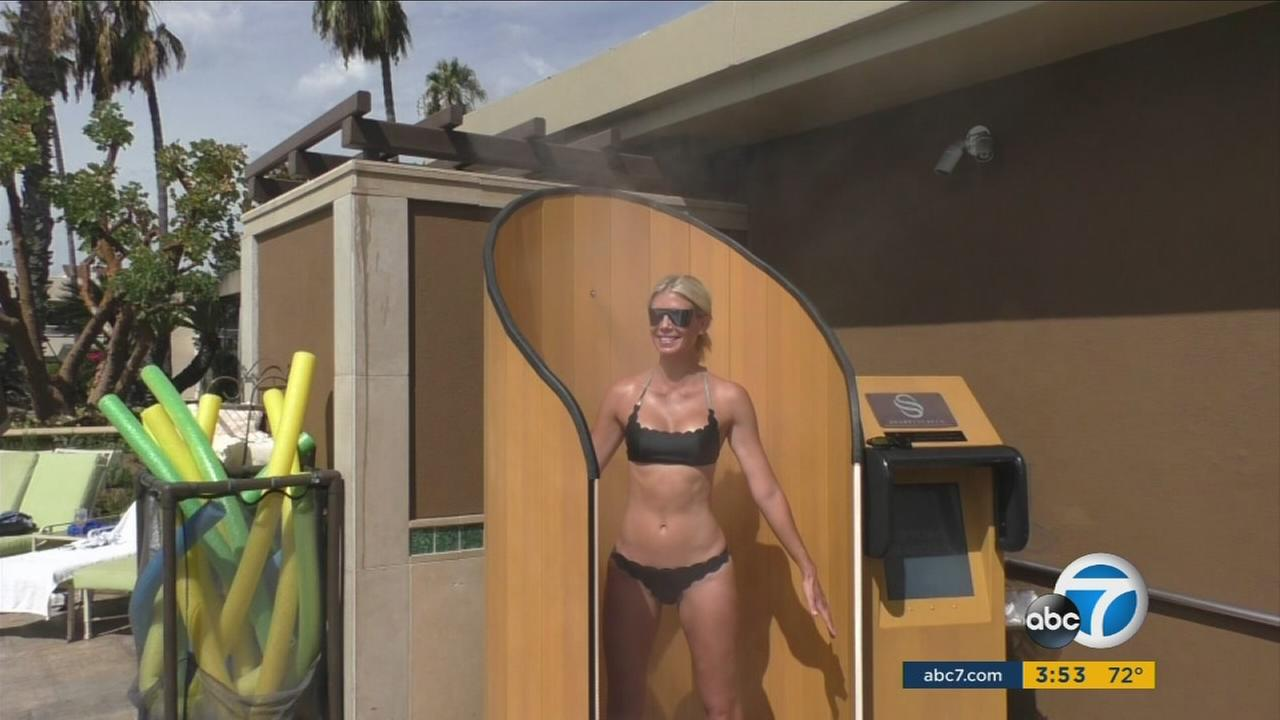 A woman gets full sunscreen coverage as she rotates on a SnappyScreen machine.