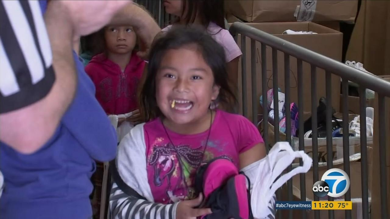 A young girl smiles from ear to ear as she receives a pair of new shoes from a mission in downtown Los Angeles on Thursday, Oct. 6, 2016.