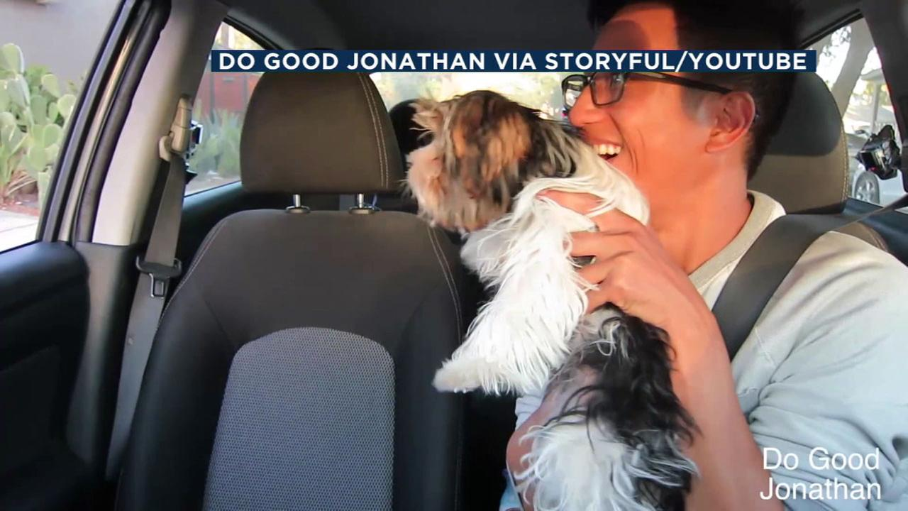 SoCal Uber driver Jonathan Gaurano holds up an adoptable puppy as a passenger enters his car.