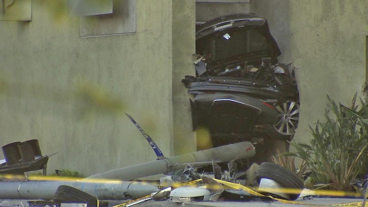 Half of a Tesla is seen wedged between two buildings after a crash in West Hollywood on Friday, July 4, 2014.