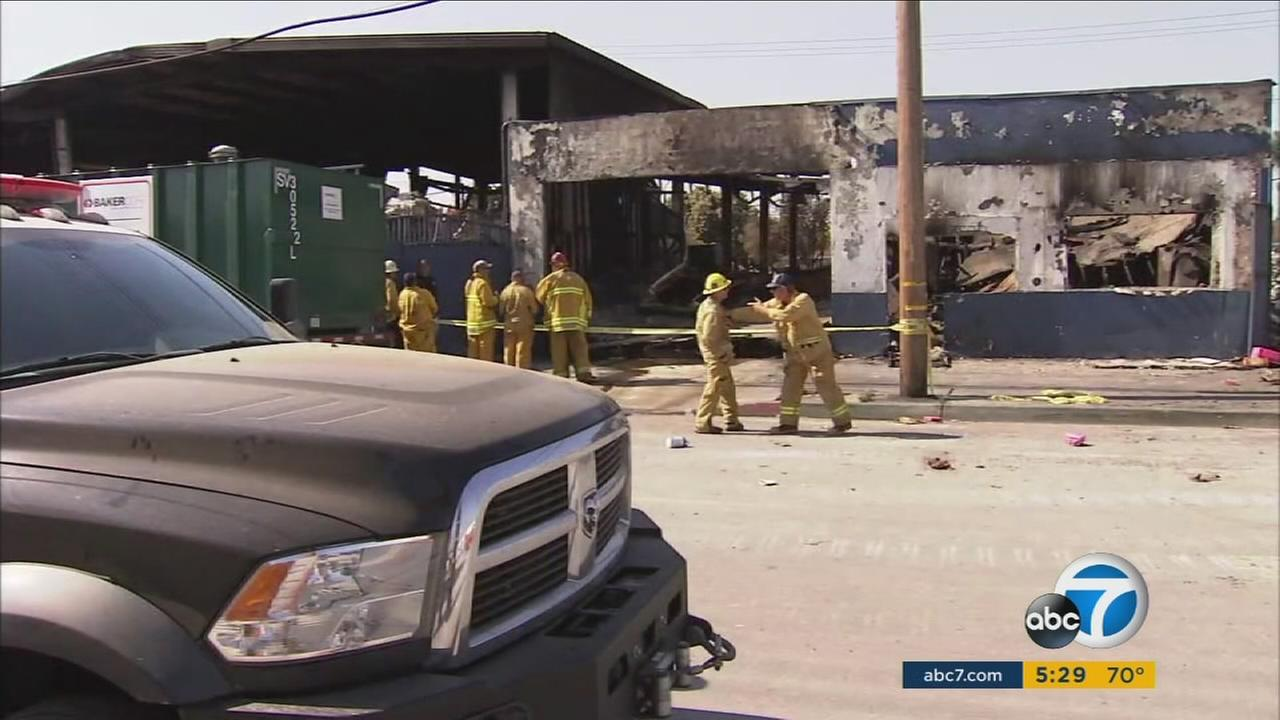 Environmental crews surround the burned-out buildings in Maywood after a magnesium fire broke out in June.
