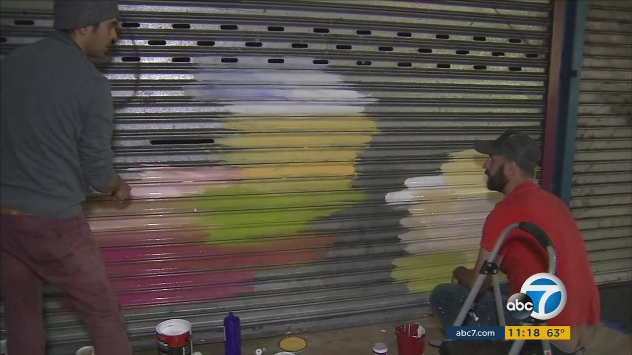 Artists from the non-profit Beautify Earth paint murals on the security shutters of businesses along Hollywood Boulevard on Wednesday, Oct. 27, 2016.