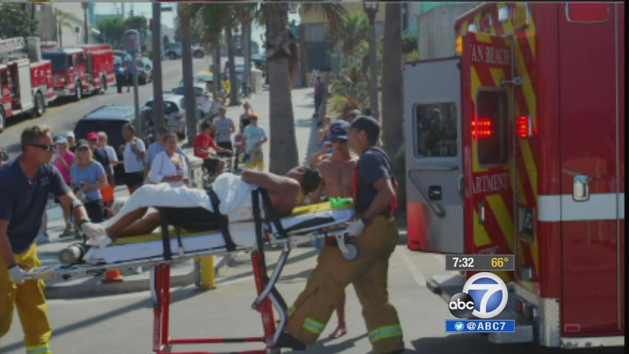 A man bitten by a shark in Manhattan Beach is carried into an ambulance on a stretcher Saturday, July 5, 2014.