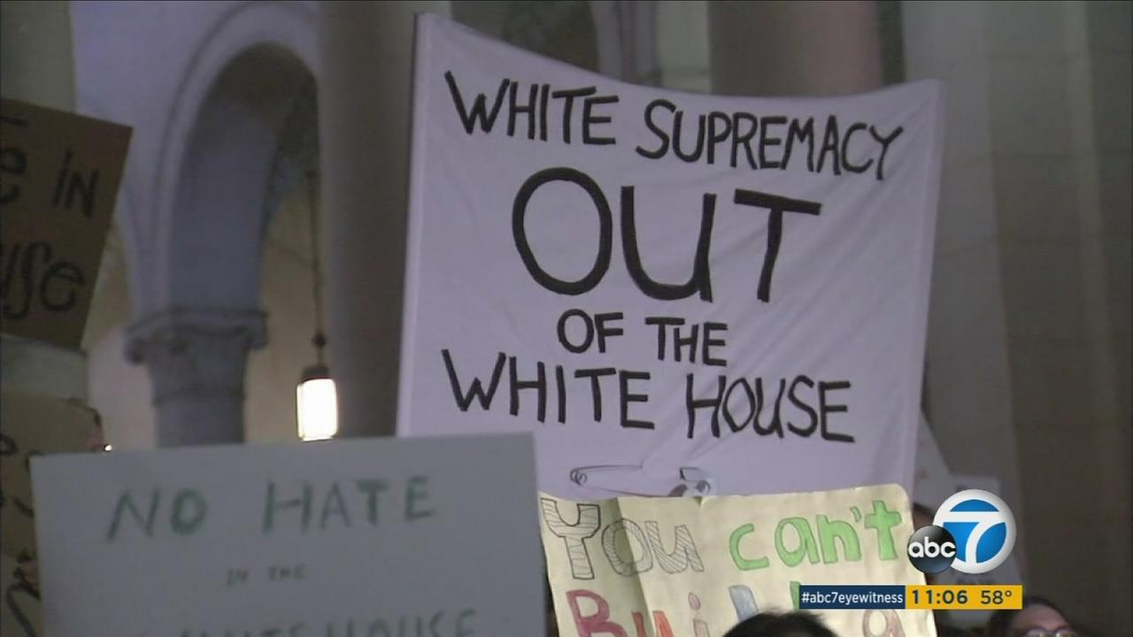 A protester at Los Angeles City Hall holds up a sign that suggest Steve Bannon is a white supremacist on Wednesday, Nov. 16, 2016.