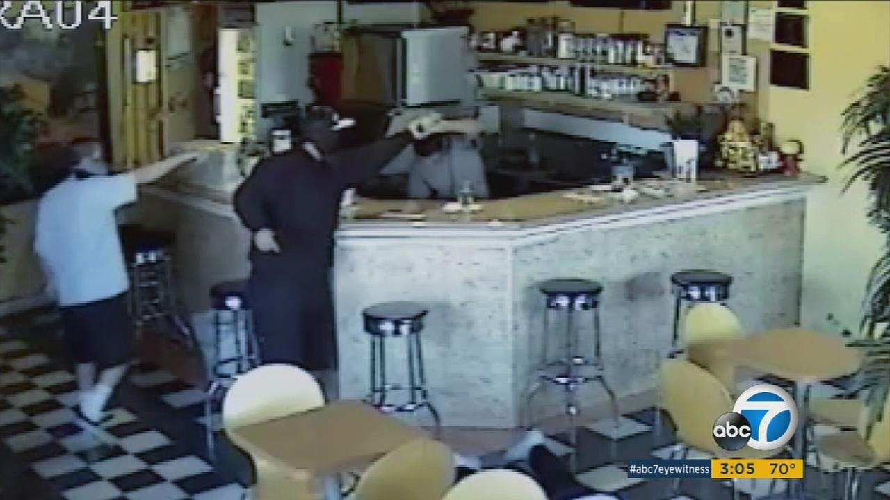 Surveillance video shows two armed suspects robbing the M and Toi Cafe in Santa Ana on Monday, Nov. 21, 2016.