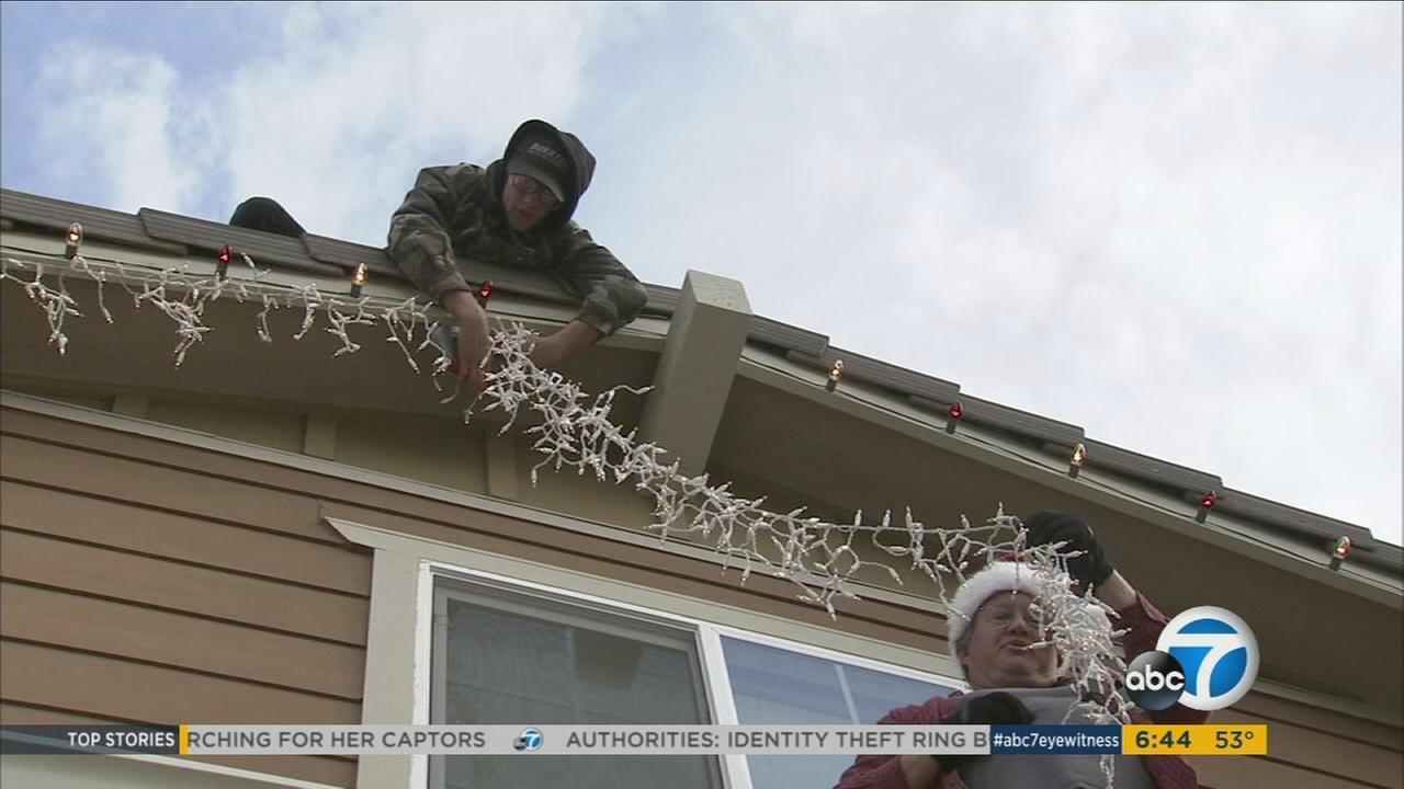Professional holiday-light installers work to illuminate a house as the season gets underway.