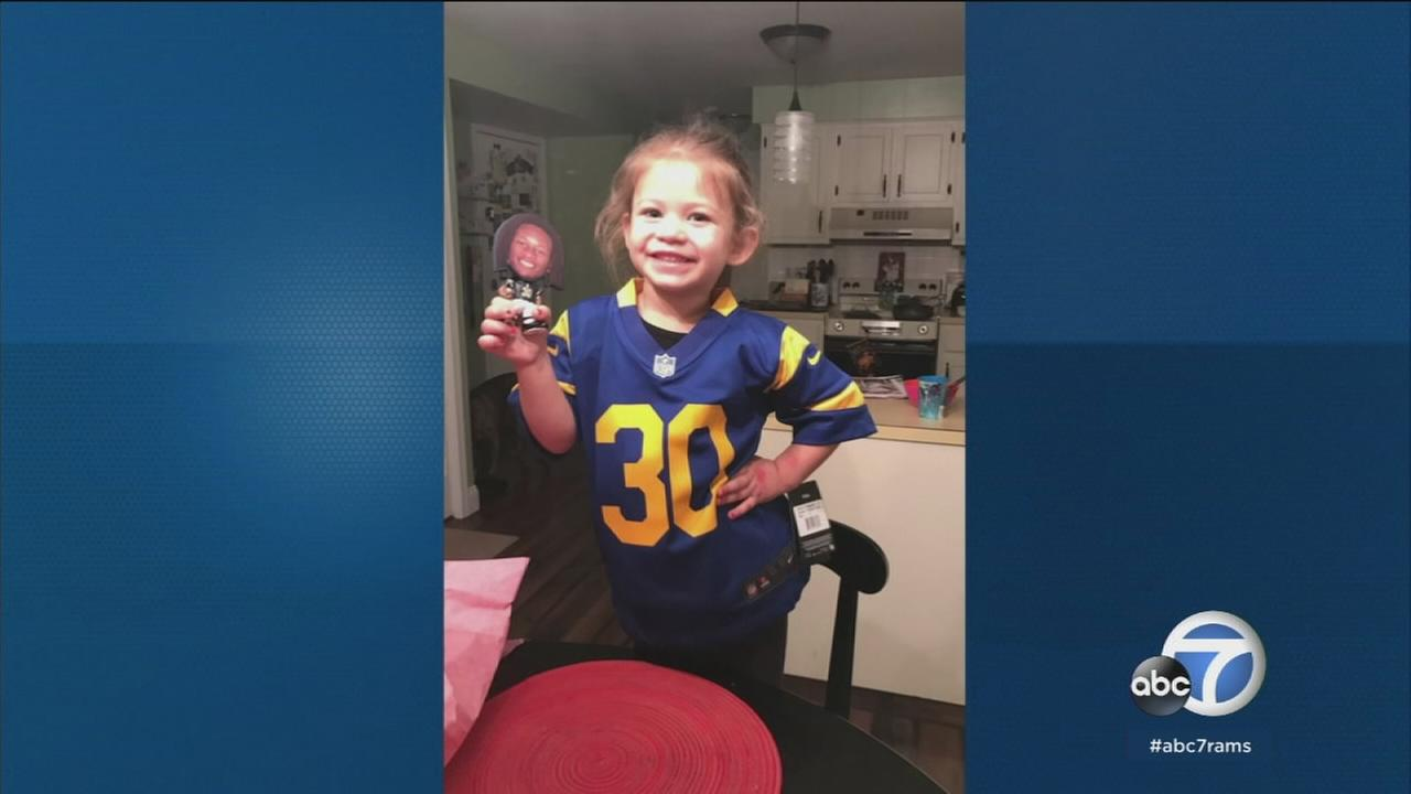 Selena, 3, holds her Todd Gurley figurine while wearing his jersey number on her birthday.