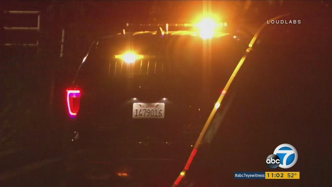 Authorities investigated the scene of a carjacking in which the victim had his car stolen near his Hollywood Hills home by a police impersonator on Tuesday, Nov. 29, 2016.