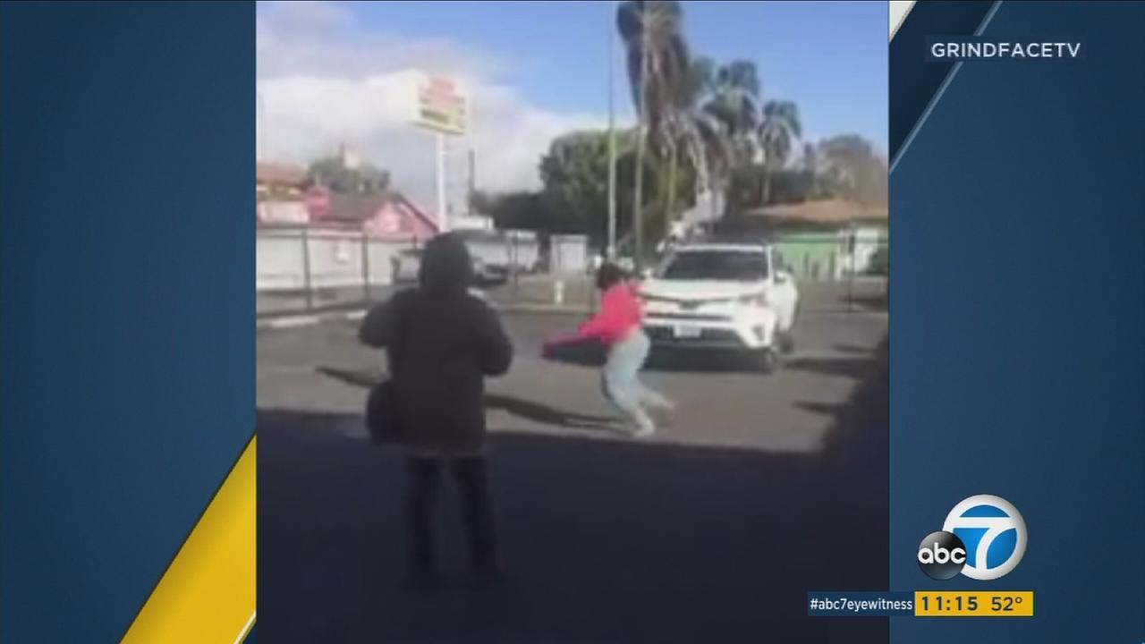 Video shows a woman running away from a car that was coming toward her during a demolition derby-style fight in South Los Angeles.