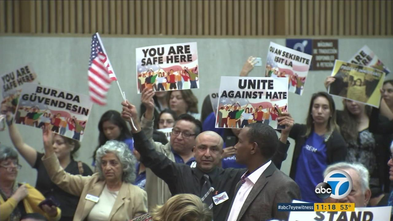 Los Angeles County residents held signs urging the board of supervisors to protect undocumented immigrants in the area.