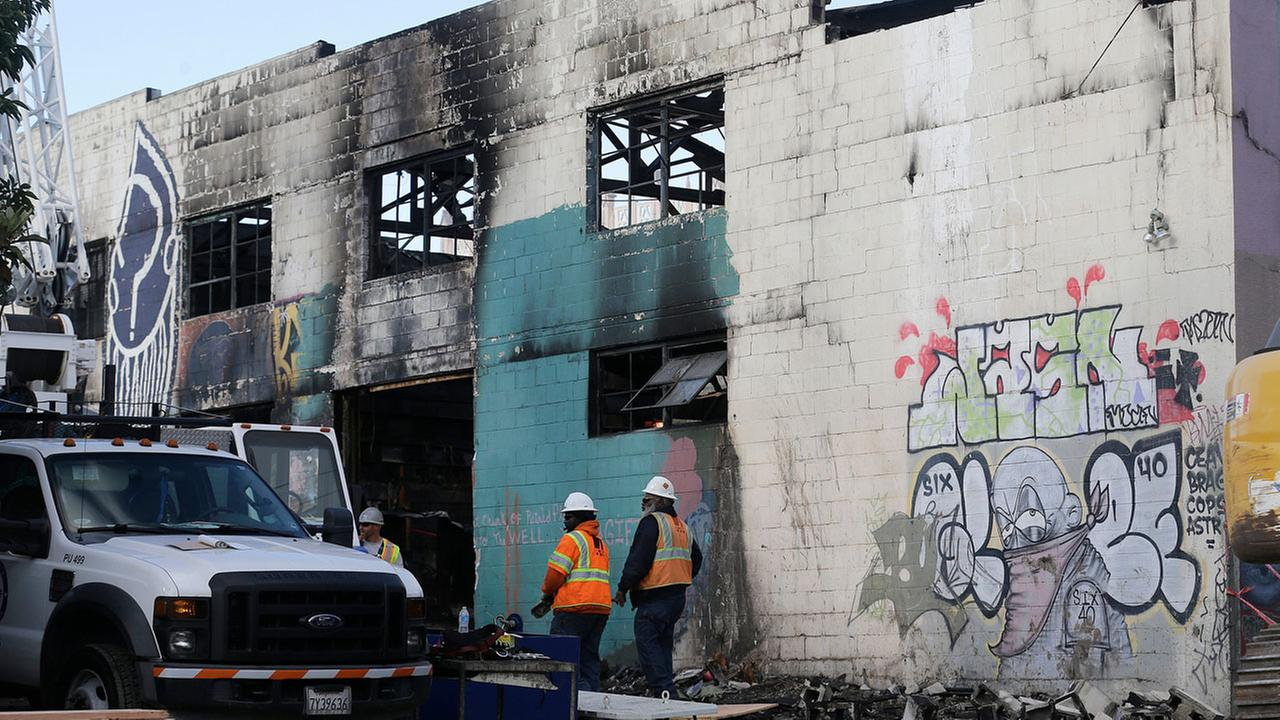 Emergency crew workers walk in front of the site of a warehouse fire in Oakland, Calif., Tuesday, Dec. 6, 2016. The fire erupted Friday, Dec. 2, killing dozens.