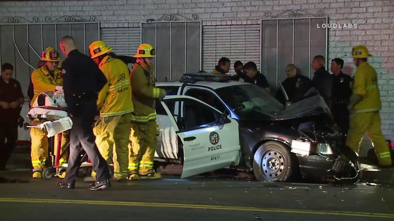 Two Los Angeles Police Department officers were transported to a hospital after their patrol car hit a light pole and slammed into a building in Mid-City Tuesday, Dec. 13, 2016.