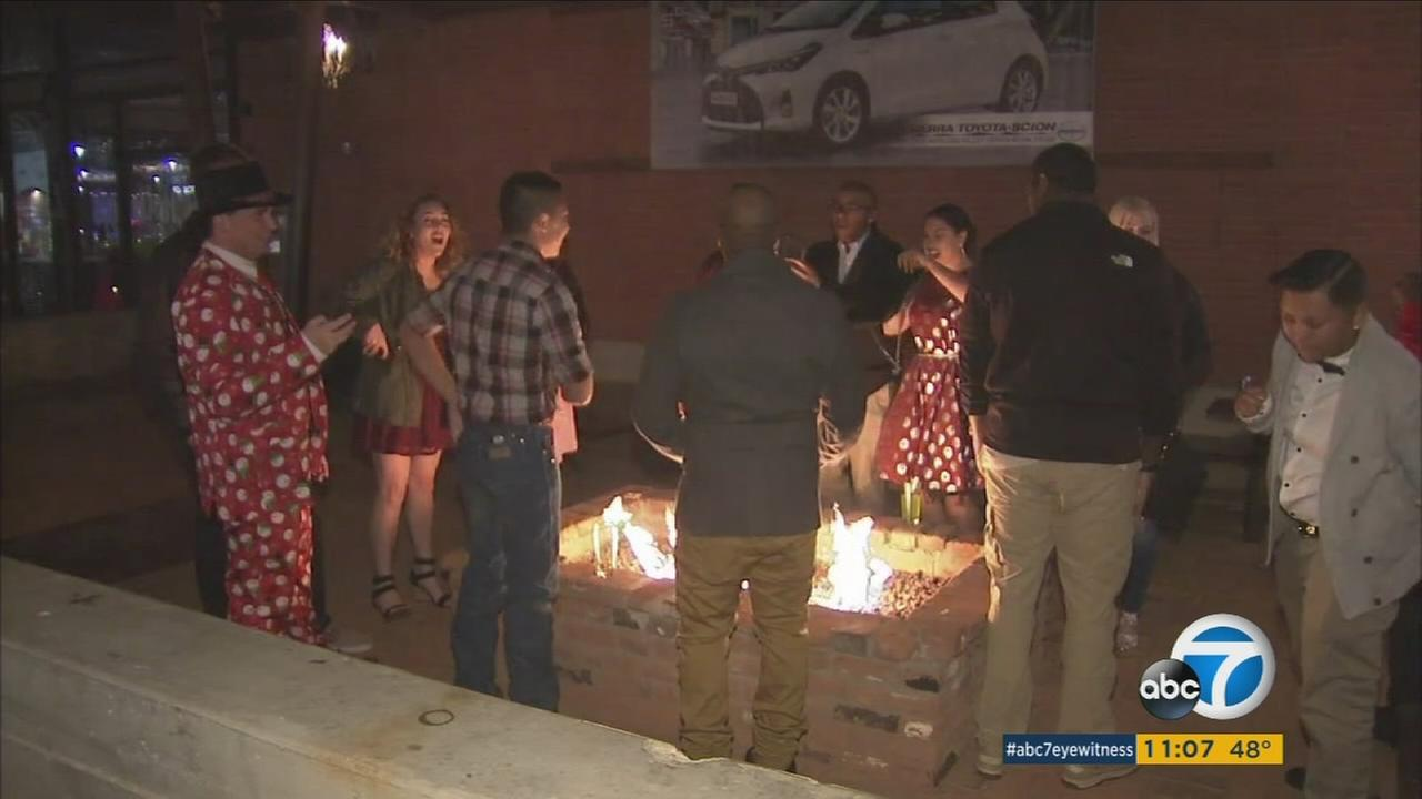 In downtown Lancaster, people gathered around an outdoor fire to stay warm as temperatures plunged below freezing.