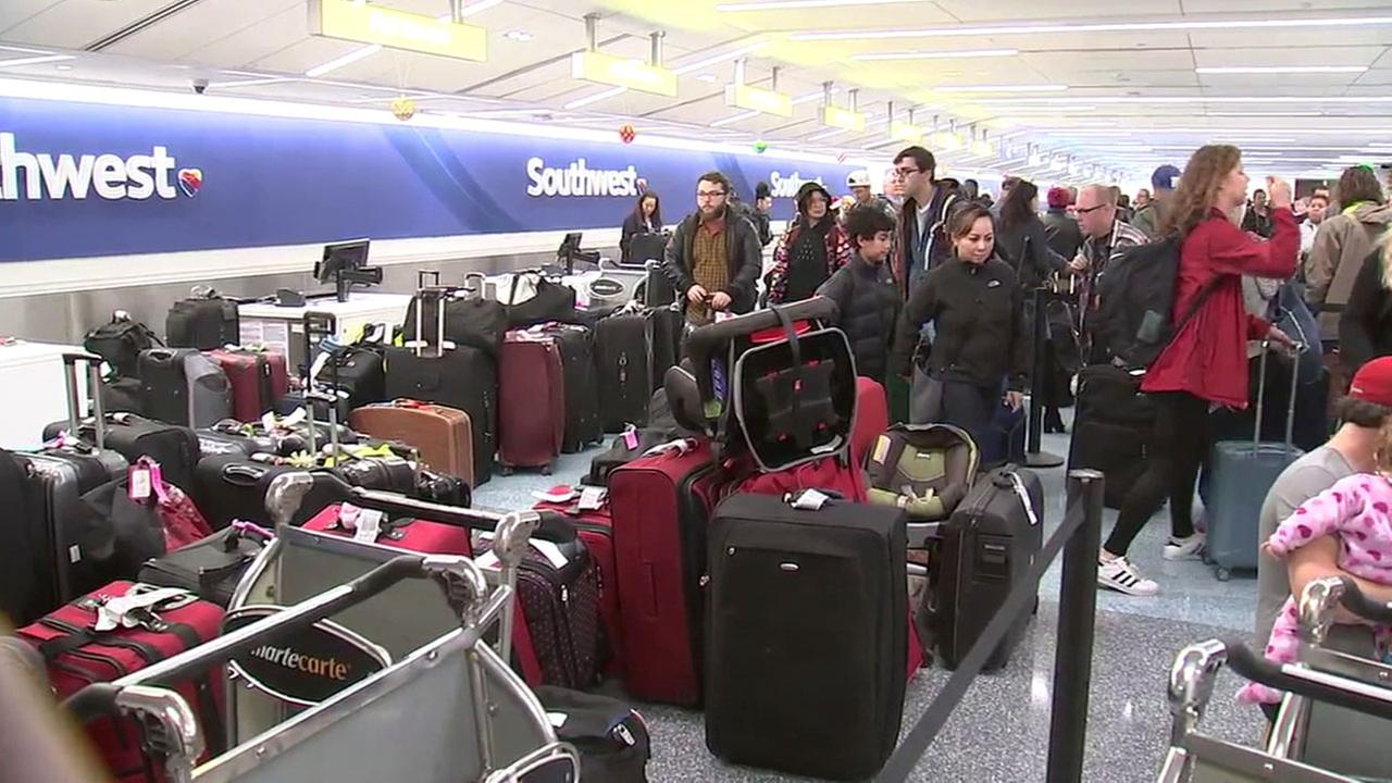 Passengers grab their bags in the Southwest terminal at Los Angeles International Airport during its busiest travel day on Wednesday, Dec. 21, 2016.