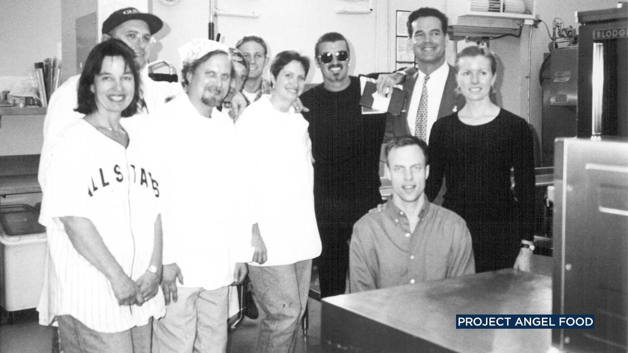 Singer George Michael poses for a photo with representatives of Project Angel Food.