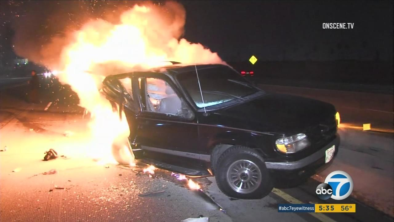 An SUV up in flames after the driver was rescued by a photographer on the 110 Freeway early Monday, Jan. 2, 2016.