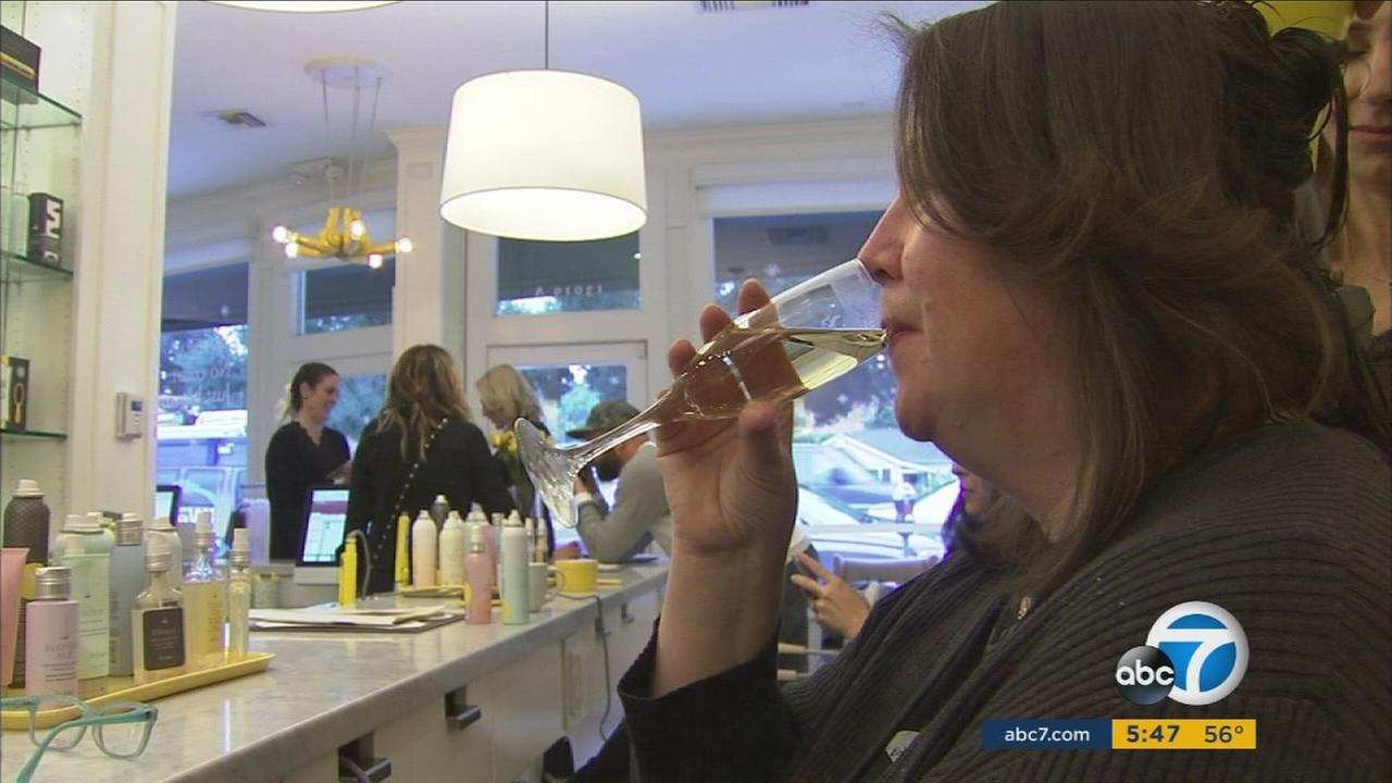A woman enjoys a glass of champagne following a new law, effective in 2017, that allows California beauty salons to provide free alcohol to customers.