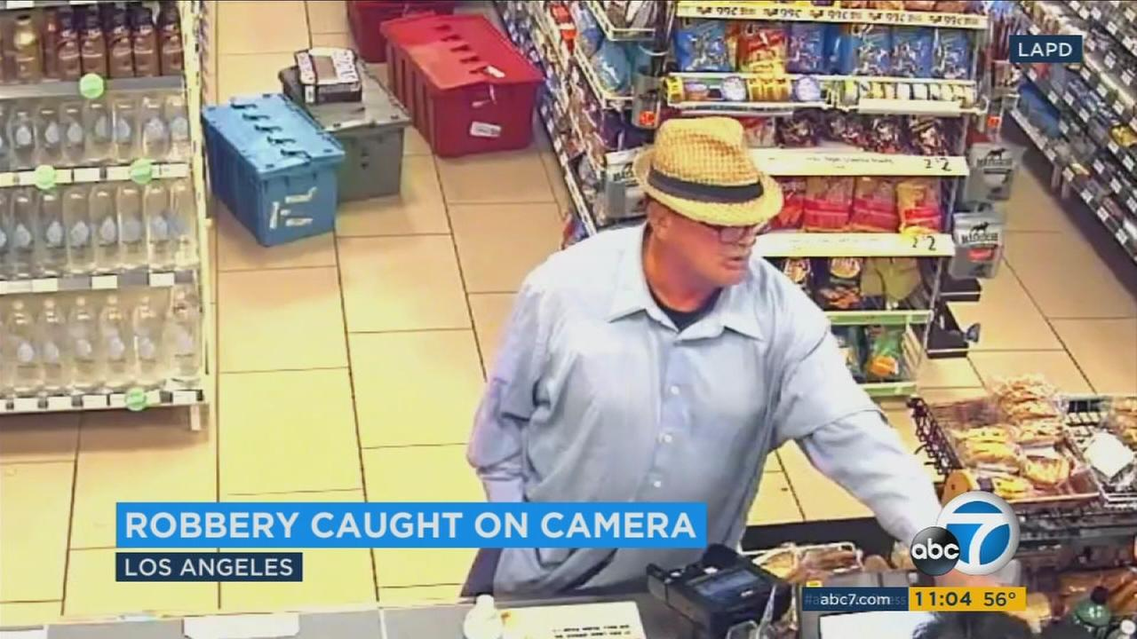 A surveillance video of a man robbing a 7-Eleven store with only his hands was released by LAPD detectives.