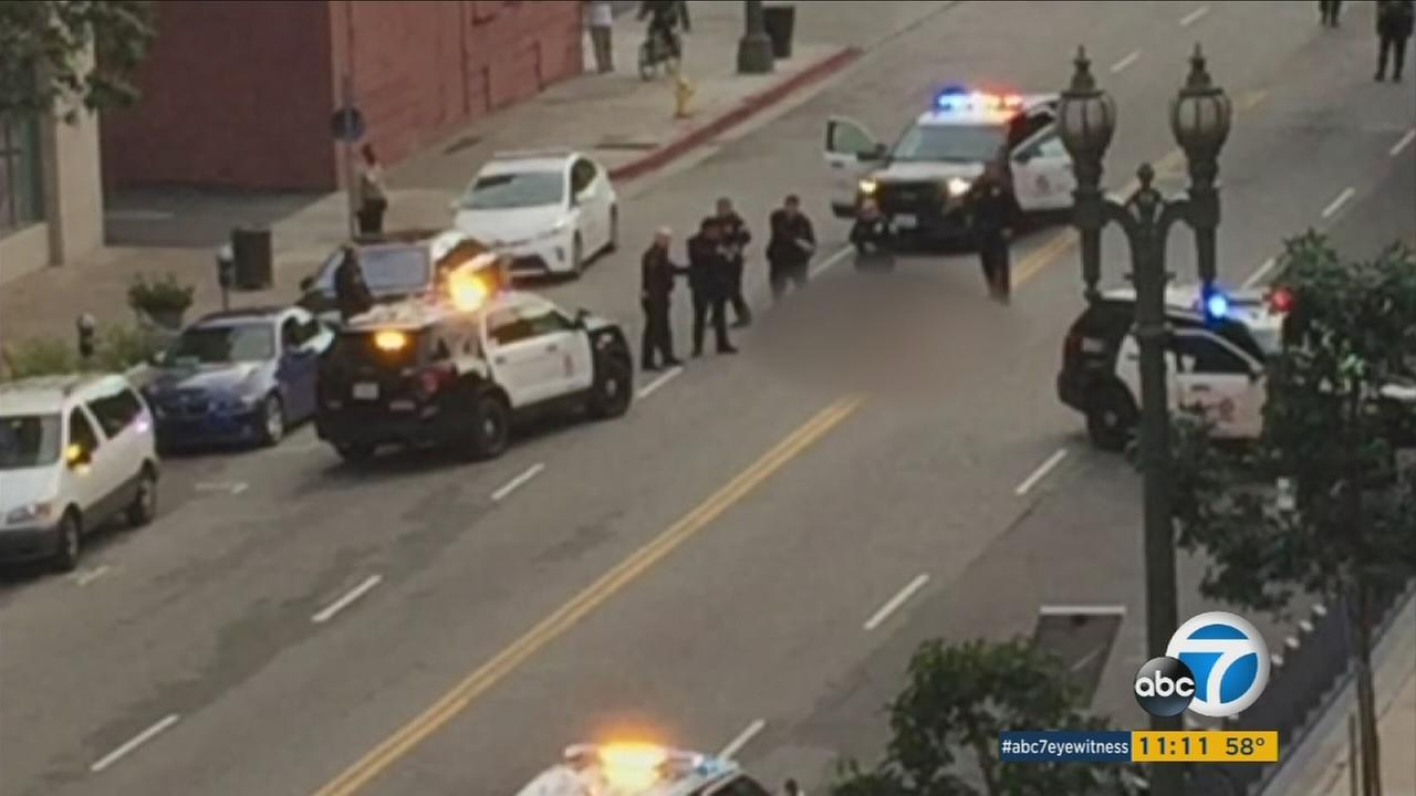 A man died in an officer-involved shooting Monday in downtown Los Angeles and police are investigating whether the death of a woman near the scene is connected to the incident.