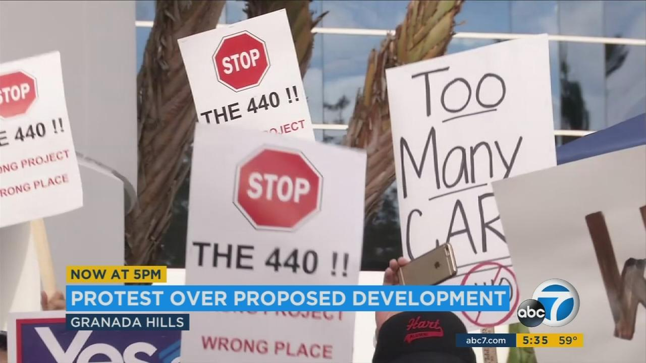Signs show Granada Hills residents protesting a proposed 440-unit mixed-use apartment complex in the area.